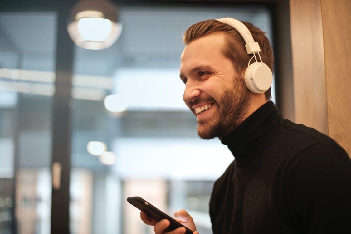 Man Wearing White Headphones Listening to Music